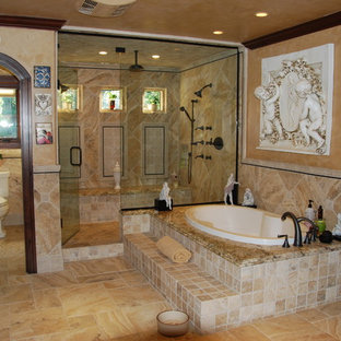 Inspiration for a large mediterranean ensuite bathroom in Orange County with a built-in bath, an alcove shower, a two-piece toilet, beige tiles, stone tiles, beige walls, travertine flooring, granite worktops and an enclosed toilet.