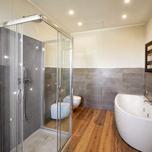 Idee per una stanza da bagno padronale minimal con doccia a filo pavimento, piastrelle grigie, porta doccia scorrevole, vasca ad angolo, bidè, pavimento in legno massello medio, pavimento marrone e pareti grigie