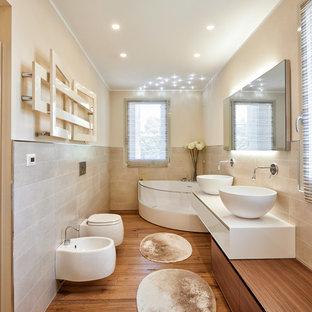 Imagen de cuarto de baño principal, actual, con armarios con paneles lisos, puertas de armario blancas, bañera esquinera, lavabo sobreencimera, bidé, baldosas y/o azulejos beige, paredes beige, suelo de madera en tonos medios, suelo marrón y encimeras blancas