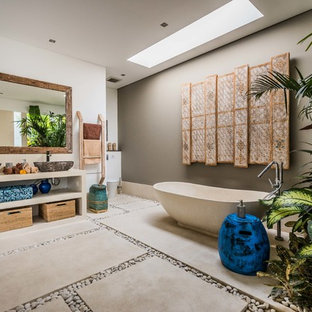 Design ideas for a tropical master bathroom in Perth with open cabinets, beige cabinets, a freestanding tub, grey walls, concrete floors, a vessel sink, grey floor and beige benchtops.