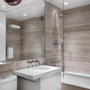 Photo of a large contemporary master bathroom in New York with flat-panel cabinets, an undermount sink, grey walls, a drop-in tub, a shower/bathtub combo, brown tile, gray tile, travertine floors, engineered quartz benchtops, a two-piece toilet, limestone, white benchtops and white cabinets.