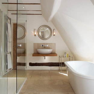 This is an example of a contemporary bathroom in West Midlands with a vessel sink, open cabinets, wood benchtops, a freestanding tub, a corner shower, beige tile, white walls and brown benchtops.