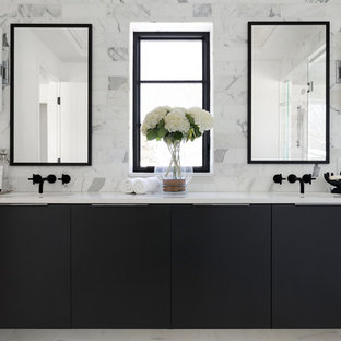Photo of a large mediterranean ensuite bathroom in Minneapolis with white tiles, white walls, marble flooring, engineered stone worktops, white floors, white worktops, flat-panel cabinets, black cabinets and marble tiles.
