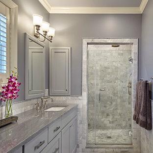 Immagine di una stanza da bagno padronale classica di medie dimensioni con lavabo sottopiano, ante grigie, top in quarzite, doccia alcova, piastrelle grigie, piastrelle in pietra, pareti grigie, pavimento con piastrelle a mosaico, ante con riquadro incassato e top grigio