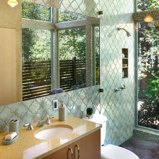 Photo of a mediterranean ensuite bathroom in San Francisco with concrete flooring, a submerged sink, flat-panel cabinets, medium wood cabinets, a built-in shower, green tiles and green walls.