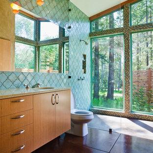 Свежая идея для дизайна: главная ванная комната среднего размера в современном стиле с душем без бортиков, врезной раковиной, плоскими фасадами, фасадами цвета дерева среднего тона, унитазом-моноблоком, зеленой плиткой, керамической плиткой, бетонным полом, столешницей из переработанного стекла и зелеными стенами - отличное фото интерьера