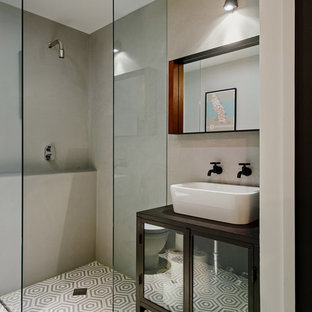 Exempel på ett litet modernt brun brunt badrum med dusch, med ett fristående handfat, luckor med glaspanel, grå kakel, cementkakel, grå väggar, betonggolv, en kantlös dusch och träbänkskiva