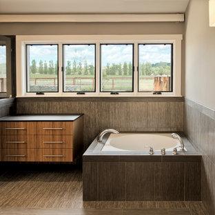 На фото: большая главная ванная комната в современном стиле с плоскими фасадами, фасадами цвета дерева среднего тона, серой плиткой, керамической плиткой, серыми стенами, полновстраиваемой ванной, полом из ламината, столешницей из искусственного камня и разноцветным полом с
