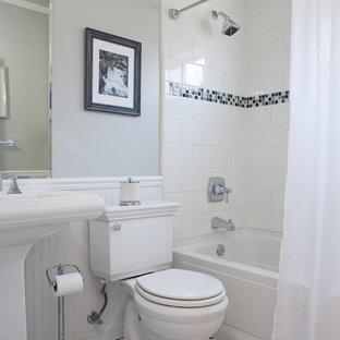 Esempio di una stanza da bagno chic di medie dimensioni con piastrelle a mosaico, lavabo a colonna, vasca ad alcova, vasca/doccia, WC a due pezzi, pavimento con piastrelle in ceramica, pareti grigie e doccia con tenda