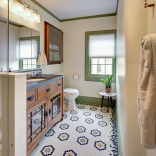 Inspiration for a mid-sized craftsman 3/4 white tile multicolored floor and mosaic tile floor corner shower remodel in New York with furniture-like cabinets, medium tone wood cabinets, a two-piece toilet, white walls, an undermount sink, granite countertops, a hinged shower door and gray countertops