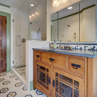Inspiration for a mid-sized arts and crafts bathroom in New York with furniture-like cabinets, medium wood cabinets, a two-piece toilet, white tile, white walls, porcelain floors, an undermount sink, granite benchtops, multi-coloured floor, a hinged shower door and grey benchtops.