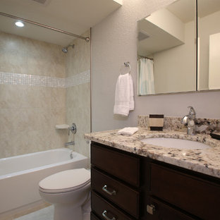 Bathroom - small coastal beige tile and porcelain tile porcelain tile bathroom idea in Tampa with an undermount sink, dark wood cabinets, granite countertops, a two-piece toilet and gray walls