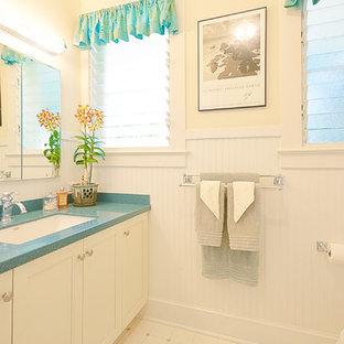 Idee per una stanza da bagno tropicale di medie dimensioni con ante in stile shaker, ante bianche, doccia ad angolo, WC a due pezzi, piastrelle bianche, pareti bianche, pavimento in linoleum, lavabo sottopiano e top in superficie solida