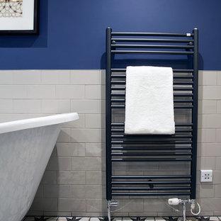 Ejemplo de cuarto de baño infantil, bohemio, de tamaño medio, con bañera exenta, ducha abierta, baldosas y/o azulejos blancos, baldosas y/o azulejos de porcelana, paredes azules, suelo de baldosas de cerámica, suelo multicolor y ducha abierta