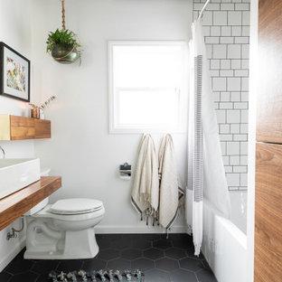 Diseño de cuarto de baño actual con bañera empotrada, baldosas y/o azulejos blancos, paredes blancas, lavabo sobreencimera, encimera de madera, suelo negro y encimeras marrones
