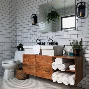 Mid-sized minimalist master white tile and ceramic tile ceramic floor and white floor bathroom photo in St Louis with furniture-like cabinets, medium tone wood cabinets, a one-piece toilet, white walls, a trough sink and wood countertops