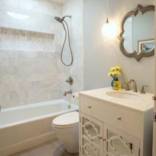 Bild på ett mellanstort eklektiskt badrum för barn, med luckor med glaspanel, vita skåp, ett badkar i en alkov, en dusch/badkar-kombination, en toalettstol med hel cisternkåpa, vit kakel, marmorkakel, grå väggar, klinkergolv i keramik, ett undermonterad handfat, bänkskiva i återvunnet glas, grått golv och dusch med duschdraperi
