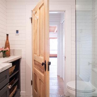 Klassisk inredning av ett litet vit vitt badrum med dusch, med skåp i shakerstil, blå skåp, en toalettstol med hel cisternkåpa, vit kakel, tunnelbanekakel, vita väggar, cementgolv, ett nedsänkt handfat, bänkskiva i kvartsit, grått golv och dusch med gångjärnsdörr