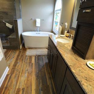Imagen de cuarto de baño principal, rural, de tamaño medio, con armarios estilo shaker, puertas de armario de madera oscura, bañera exenta, ducha esquinera, baldosas y/o azulejos marrones, paredes beige, suelo vinílico, lavabo encastrado y encimera de granito