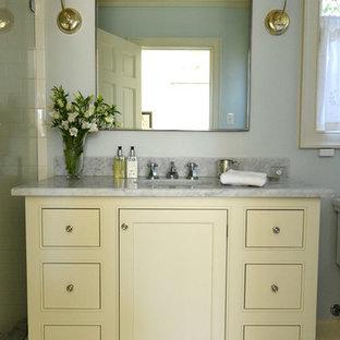 Mittelgroßes Klassisches Duschbad mit Kassettenfronten, gelben Schränken, Duschnische, Toilette mit Aufsatzspülkasten, weißen Fliesen, Metrofliesen, blauer Wandfarbe, Mosaik-Bodenfliesen, Unterbauwaschbecken und Marmor-Waschbecken/Waschtisch in San Diego