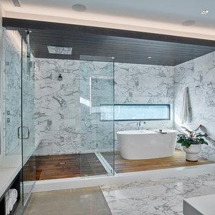 Inspiration för stora moderna vitt en-suite badrum, med ett fristående badkar, en hörndusch, vita väggar, dusch med gångjärnsdörr, släta luckor, svarta skåp, ett integrerad handfat och bänkskiva i akrylsten