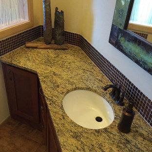 Diseño de cuarto de baño clásico renovado, grande, con armarios con paneles lisos, puertas de armario de madera oscura, baldosas y/o azulejos marrones, suelo de linóleo, lavabo bajoencimera y encimera de granito