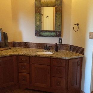 Imagen de cuarto de baño clásico renovado, grande, con lavabo bajoencimera, armarios con paneles lisos, puertas de armario de madera oscura, encimera de granito, baldosas y/o azulejos marrones, baldosas y/o azulejos de vidrio y suelo de linóleo