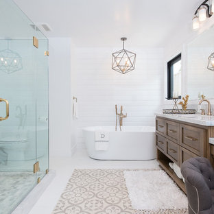 Example of a large cottage master white tile and subway tile white floor freestanding bathtub design in Orange County with shaker cabinets, brown cabinets, a one-piece toilet, white walls, an integrated sink, granite countertops, a hinged shower door and white countertops