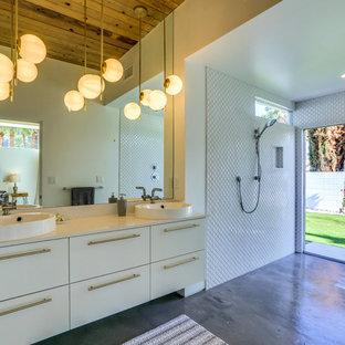 Foto di una stanza da bagno minimalista con ante lisce, ante bianche, doccia a filo pavimento, piastrelle bianche, piastrelle a mosaico, pareti bianche, pavimento in cemento, lavabo a bacinella, pavimento grigio, doccia aperta e top bianco