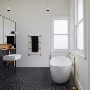 Inspiration for a small contemporary bathroom in Melbourne with a freestanding tub, white tile, white walls, mosaic tile floors and black floor.