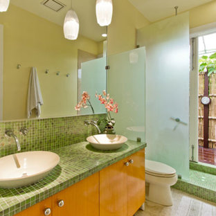 Стильный дизайн: главная ванная комната среднего размера в современном стиле с настольной раковиной, плоскими фасадами, фасадами цвета дерева среднего тона, открытым душем, раздельным унитазом, зеленой плиткой, стеклянной плиткой, желтыми стенами, полом из травертина и столешницей из плитки - последний тренд