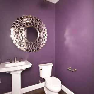 Inspiration för ett funkis badrum, med ett piedestal handfat, en toalettstol med separat cisternkåpa, lila väggar och mörkt trägolv
