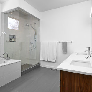 Photo of a medium sized modern ensuite bathroom in Edmonton with a submerged sink, grey floors, flat-panel cabinets, medium wood cabinets, a submerged bath, a corner shower, grey tiles, stone tiles, white walls, laminate floors, engineered stone worktops and a hinged door.