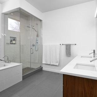 Inspiration för ett mellanstort funkis en-suite badrum, med ett undermonterad handfat, grått golv, släta luckor, skåp i mellenmörkt trä, ett undermonterat badkar, en hörndusch, grå kakel, stenkakel, vita väggar, laminatgolv, bänkskiva i kvarts och dusch med gångjärnsdörr