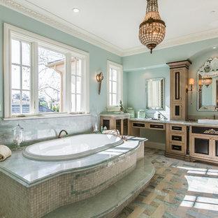 Mediterranes Badezimmer mit Schrankfronten mit vertiefter Füllung, hellbraunen Holzschränken, Einbaubadewanne, blauer Wandfarbe, Einbauwaschbecken, buntem Boden und grüner Waschtischplatte in Los Angeles