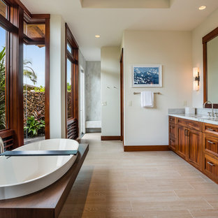 Inspiration for a tropical porcelain floor and beige floor freestanding bathtub remodel in Hawaii with shaker cabinets, medium tone wood cabinets, beige walls, an undermount sink and quartzite countertops