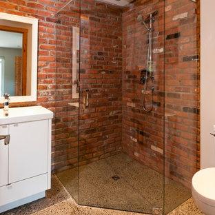 バンクーバーの大きいコンテンポラリースタイルのおしゃれなバスルーム (浴槽なし) (フラットパネル扉のキャビネット、白いキャビネット、コーナー設置型シャワー、一体型トイレ、一体型シンク、赤い壁、コンクリートの床) の写真