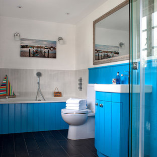 Medium sized beach style family bathroom in Other with blue cabinets, a two-piece toilet, white walls, black floors, a built-in bath, a shower/bath combination and grey tiles.