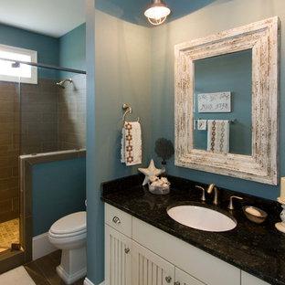 Foto di una stanza da bagno stile marinaro con lavabo sottopiano, ante con riquadro incassato, ante beige, doccia alcova e piastrelle marroni