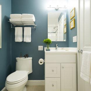 Foto di una piccola stanza da bagno con doccia tradizionale con ante bianche, WC monopezzo, piastrelle bianche, ante in stile shaker, vasca ad alcova, vasca/doccia, piastrelle in gres porcellanato, pareti blu, pavimento in travertino, lavabo sottopiano e top in superficie solida
