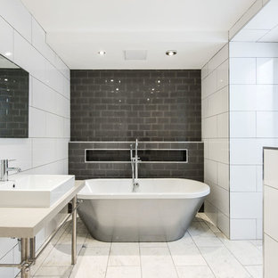 Contemporary bathroom in Other with a freestanding bath, grey tiles, white tiles and metro tiles.
