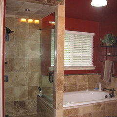 mediterranean bathroom Walk in shower with frameless shower door, and travertine tile