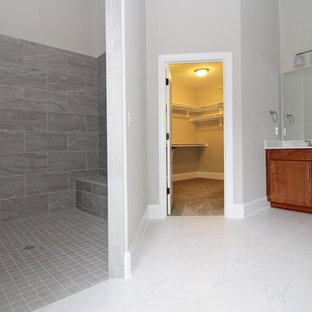 Modelo de cuarto de baño principal, actual, grande, con armarios estilo shaker, puertas de armario de madera oscura, ducha abierta, sanitario de una pieza, baldosas y/o azulejos blancos, baldosas y/o azulejos de cerámica, paredes grises, suelo de baldosas de cerámica, lavabo integrado y encimera de acrílico