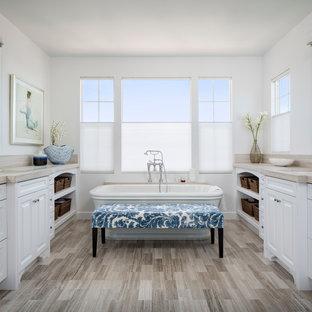Источник вдохновения для домашнего уюта: большая главная ванная комната в морском стиле с фасадами с выступающей филенкой, белыми фасадами, отдельно стоящей ванной, серой плиткой, керамогранитной плиткой, белыми стенами, врезной раковиной, столешницей из дерева, раздельным унитазом, светлым паркетным полом и бежевой столешницей