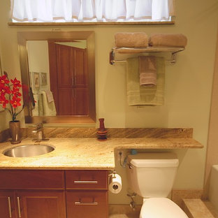Mid-sized trendy beige tile and porcelain tile porcelain tile bathroom photo in Hawaii with a vessel sink, recessed-panel cabinets, medium tone wood cabinets, granite countertops, a two-piece toilet and white walls
