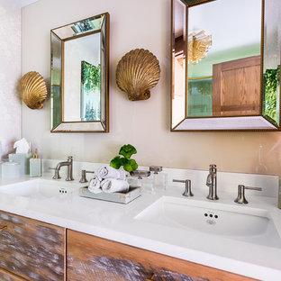 Immagine di una piccola stanza da bagno eclettica con consolle stile comò, ante con finitura invecchiata, piastrelle beige, lastra di vetro, pareti beige, top in superficie solida, top bianco e lavabo sottopiano