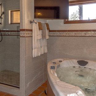 Immagine di una grande stanza da bagno padronale con vasca idromassaggio, doccia alcova, piastrelle grigie, piastrelle in pietra, pareti bianche, pavimento in cementine, top in granito, pavimento arancione e porta doccia a battente