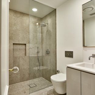 Bathroom - mid-sized modern blue tile and glass sheet ceramic floor and white floor bathroom idea in Dallas with flat-panel cabinets, gray cabinets, a wall-mount toilet, white walls, an integrated sink, quartzite countertops and a hinged shower door