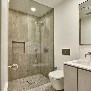 ダラスの中サイズのモダンスタイルのおしゃれな浴室 (フラットパネル扉のキャビネット、グレーのキャビネット、段差なし、壁掛け式トイレ、青いタイル、ガラス板タイル、白い壁、セラミックタイルの床、一体型シンク、珪岩の洗面台、置き型浴槽、白い床、開き戸のシャワー) の写真