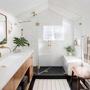 Diseño de cuarto de baño clásico renovado con armarios con paneles lisos, puertas de armario de madera oscura, ducha empotrada, baldosas y/o azulejos blancos, paredes blancas, lavabo bajoencimera, suelo negro y encimeras blancas